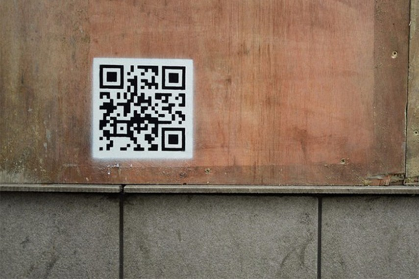 QR code as part of the Banksy's stencil, leading the viewer to a video of the police raid in the camp