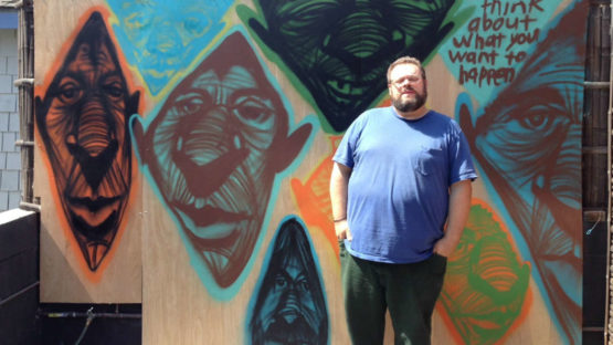 Rich Jacobs in front of his mural, Image via Laguna Beach Magazine
