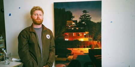 Seth Armstrong in front of his artwork