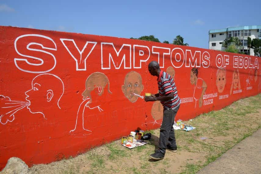 Street artist Stephen Doe paints an educational mural about Ebola in Liberia, 2014