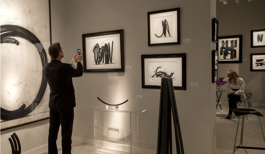 Image of a customer at art sales who photographs the piece, as buyers often do this to set the price later