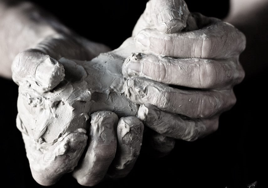 Unshaped-Clay-in-Potters-Hands before making, firing and application of glaze.In studio different glazes can be applied in making of pottery.Potters make great pottery work by firing pottery and through the use of glaze.