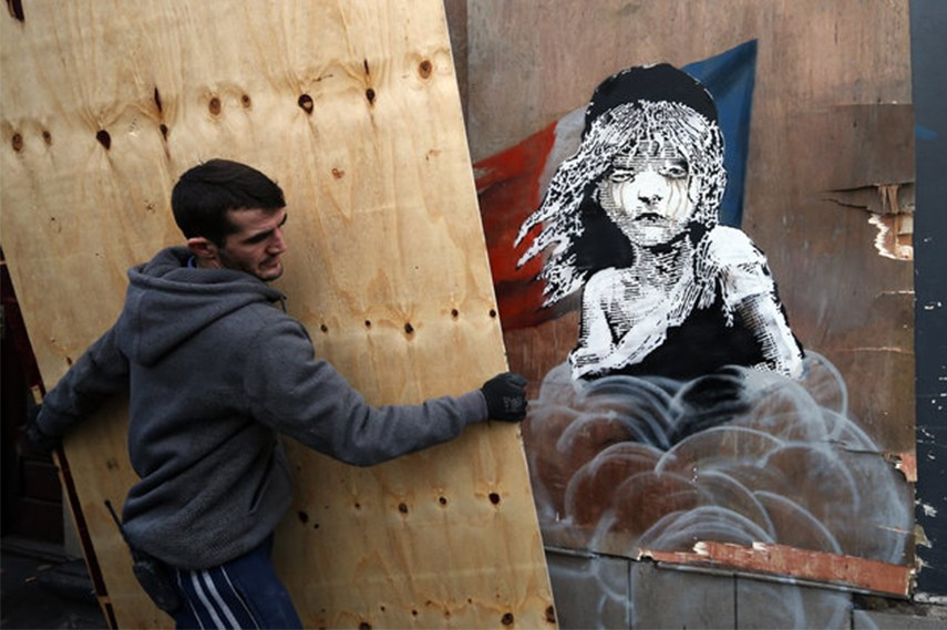 Worker covering up Banksy's artwork