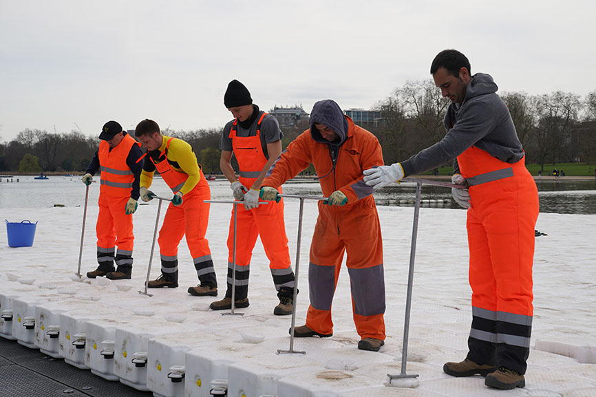 The workers screw together the cubes and pins to form the floating platform